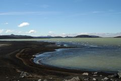 Hálslón lake with black volcanic beach and snow capped mountains in Iceland royalty free stock photo