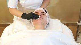 Hände des Kosmetikers wischen die Mädchen gegenüberstellen im Badekurortsalon mit weißen Servietten ab stock footage