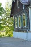 Härlig sikt i trädgården av ett gammalt charmigt brunt trähus och träd royaltyfri foto