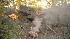Höhlenbewohner, männlicher Junge, der ursprüngliche Steinwaffe im Lager herstellt stock footage