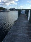 Hölzernes Dock und weiße Boots-blauer Himmel in Florida-Jachthafen lizenzfreie stockbilder