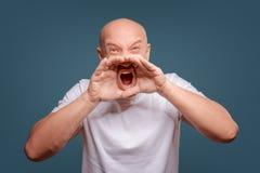 Hübscher glücklicher Mann tragendes weißes T-Shirt, Kerl, der laut, lokalisiert auf blauem Hintergrund spricht stockfoto