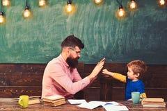 Hübscher Lehrer und nettes Kind, die im Klassenzimmer spielt Schüler, der die Aufgabe erzielt Kleiner Meistergruß stockbild