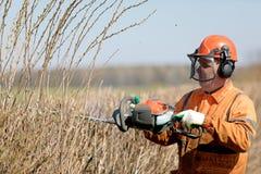 H?ckbr?m och besk?raservice Den yrkesm?ssiga landscaperen Worker Cutting Hedgerows med gas drev sax arkivfoton