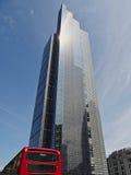 Hägertorn och röd London buss Fotografering för Bildbyråer
