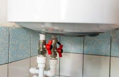 Hähne des heißen und kalten Wassers auf elektrischem Warmwasserbereitungskessel stockbilder