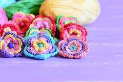 Häkelarbeitblumen verschönert mit Knöpfen und Perlen Schöne Häkelarbeitblumen, farbiges Baumwollgarn auf purpurrotem Holztisch stockbild