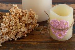 Häkelarbeitvalentinsgrußherz auf Kerze mit Blumen Lizenzfreie Stockbilder