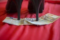 Häl av svarta skor på banknot för euro 50 på röd säng Fotografering för Bildbyråer