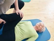 Hälerigymnastik för äldre kvinna från hennes personliga traine Fotografering för Bildbyråer