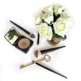 Hälfte benutzte Pulver mit Bürsten, Blumenstrauß der weißen Rosen lizenzfreie stockfotografie