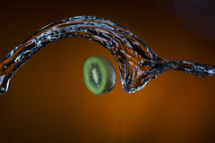 Hälfte der Kiwi und des Spritzens des Wassers auf orange Hintergrund Lizenzfreies Stockbild