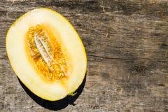 Hälfte der Melone auf rustikalem hölzernem Hintergrund Stockfotografie