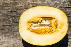 Hälfte der Melone auf rustikalem hölzernem Hintergrund Stockfoto