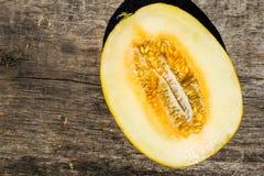 Hälfte der Melone auf rustikalem hölzernem Hintergrund Stockbild