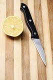 Hälfte der Zitrone auf hölzernem Küchevorstand und -messer Stockfoto