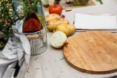 Hälfte der Zwiebel besprühen mit ฺBlack Pfeffer mit Kartoffeln mit hölzernem Block auf dem Tisch mit Tablocloth Lizenzfreies Stockbild
