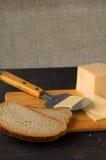 Hälfte ein Brötchen mit Käse und undeutlichen Brötchen im Hintergrund Lizenzfreies Stockfoto