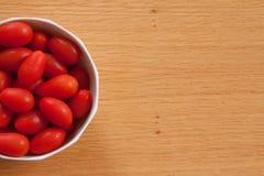 Hälfte eine Schüssel von Cherry Tomatoes auf einer Tabelle lizenzfreie stockfotografie