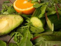 Hälfte einer Avocado mit grünem Kopfsalat, Gurke und einer Orange Lizenzfreie Stockbilder