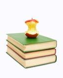 Hälfte-gegessener Apfel auf einem Stapel Büchern Stockbilder
