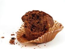 Hälfte gegessenes Schokoladenmuffin in der Verpackung Stockbilder