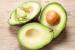 Hälfte geschnittene Avocado auf hölzernem Schnittbrett stockfotografie