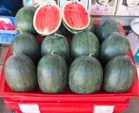 Hälfte schnitt den Wassermelone eingewickelten schützenden Film, der am lokalen Bauernhofmarkt verkauft wurde Stockfotos