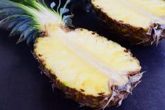 Hälften von Ananas auf schwarzem konkretem Hintergrund stockfoto