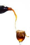 Häll cola in i ett exponeringsglas Arkivfoto