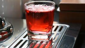 Häll den söta röda drinken in i exponeringsglas stock video