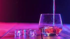 Häll en stark doftande whisky i exponeringsglaskopp med iskuber färgbelysning arkivfilmer