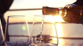 Häll smakligt vitt vin på solnedgången vid havet HD 1920x1080 långsam rörelse arkivfilmer
