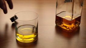 H?ll whisky fr?n flaskan in i exponeringsglas p? tabellen stock video