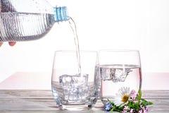 Hälla av mineraliskt drinkvatten för mousserande sodavatten i exponeringsglas med ic arkivfoto
