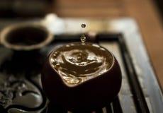 Hälla av utsökt grönt te från tekannan på teceremoni för traditionell kines Uppsättning av utrustning för att dricka te Royaltyfri Fotografi