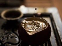 Hälla av utsökt grönt te från tekannan på teceremoni för traditionell kines Uppsättning av utrustning för att dricka te Royaltyfria Bilder