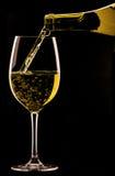 Hälla ett exponeringsglas av vin på svart bakgrund Arkivbild