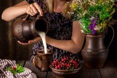Hälla för flicka mjölkar från en tillbringare in i en kopp och en bunke med bär på en trätabell blommar tillbringaren royaltyfri foto