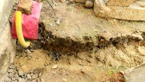 Hälla som lägger betong in i fundament av huset genom att använda skyffeln av cement och stenar Bygga konkret arbete i grund arkivfilmer