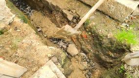 Hälla som lägger betong in i fundament av huset genom att använda skyffeln av cement och stenar Bygga konkret arbete i grund stock video