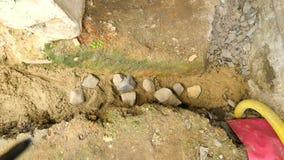 Hälla som lägger betong in i fundament av huset genom att använda skyffeln av cement och stenar Bygga konkret arbete i grund lager videofilmer