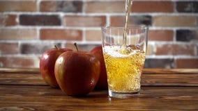 Hällande äppelcider i exponeringsglas på köket stock video