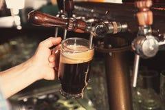 Hällande öl för bartender från klappet in i exponeringsglas i stång arkivfoton
