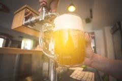 Hällande öl för bartender in i exponeringsglas i restaurangen, bar, stång fotografering för bildbyråer