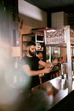 Hällande öl för bartenderWorking At Bar bar i exponeringsglas Royaltyfri Foto