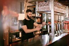 Hällande öl för bartenderWorking At Bar bar i exponeringsglas Arkivbild