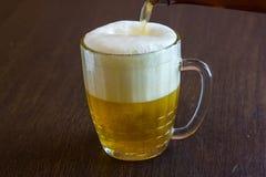 Hällande öl från flaskan in i rånar på stången Arkivfoto