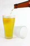 Hällande öl in i exponeringsglas Fotografering för Bildbyråer