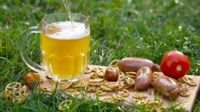 Hällande öl med kringlan, korvar och tomater royaltyfria bilder